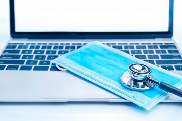 Medyczny stetoskop do kontroli lekarza na laptopie z medycznymi maskami na twarz jako pojęciem medycznym