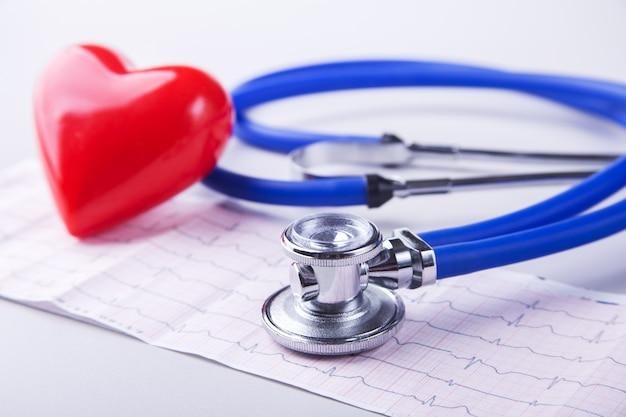 Medyczny stetoskop i czerwone serce leżące na wykresie kardiogram
