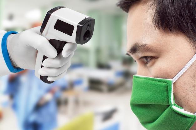 Medyczny termometr na podczerwień w ręce lekarza mierzącego temperaturę azjatyckiego mężczyzny ma na twarzy ochronną maskę chirurgiczną, wirus corona, covid-19.