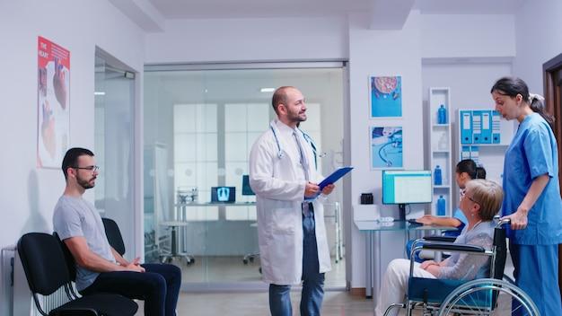 Medyk rozmawiający z niepełnosprawną kobietą w poczekalni szpitala, zapraszając pacjenta do sali egzaminacyjnej. młody człowiek czeka na konsultację z lekarzem. służba zdrowia i personel medyczny
