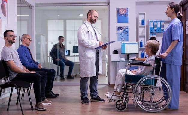 Medyk rozmawiający z niepełnosprawną kobietą w szpitalnej poczekalni, czytający formularz rejestracyjny ze schowka