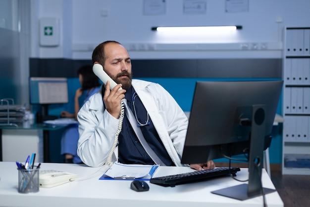 Medyk używający telefonu stacjonarnego do zdalnej komunikacji w godzinach nadliczbowych