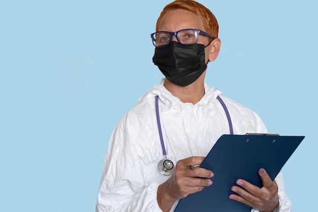 Medyk w kombinezonie ochronnym trzyma tabliczkę z formularzem opisu diagnozy
