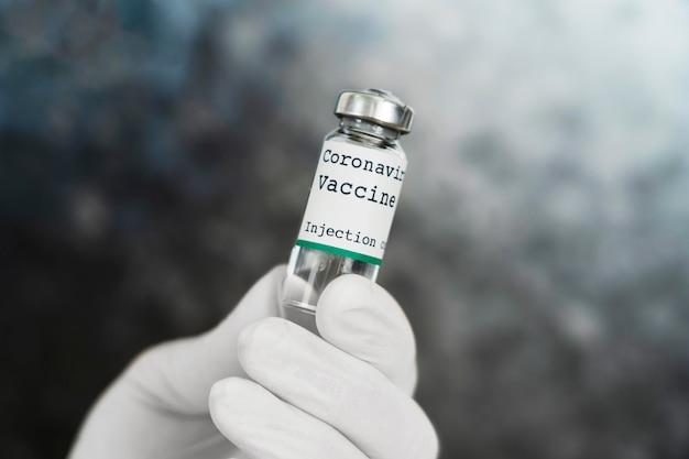 Medyk w lateksowych rękawiczkach trzymający fiolkę ze szczepionką