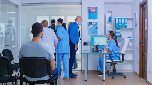 Medyk z przyłbicą przeciw covidowi 19 wzywający pacjenta do gabinetu. starszy mężczyzna z maską w szpitalnej poczekalni rozmawia z pielęgniarką. niepełnosprawna kobieta z ramą zimmer.