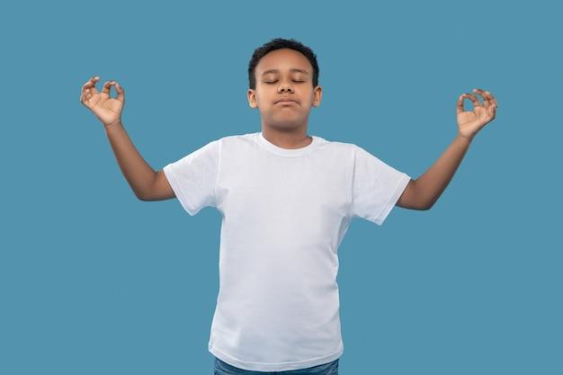 Medytacja. afroamerykański chłopiec w wieku szkolnym z zamkniętymi oczami i rękami do boków, stojący spokojnie medytując