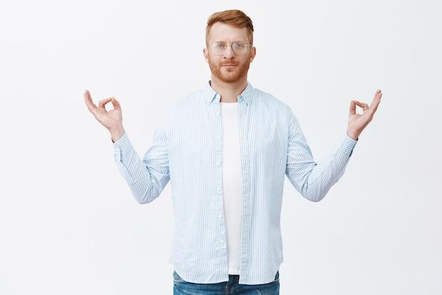 Medytacja i spokojne myśli. zrelaksowany i przystojny facet z rudymi włosami w okularach i swobodnym stroju, rozkładający ręce w geście zen, stojący w pozie jogi na szarej ścianie
