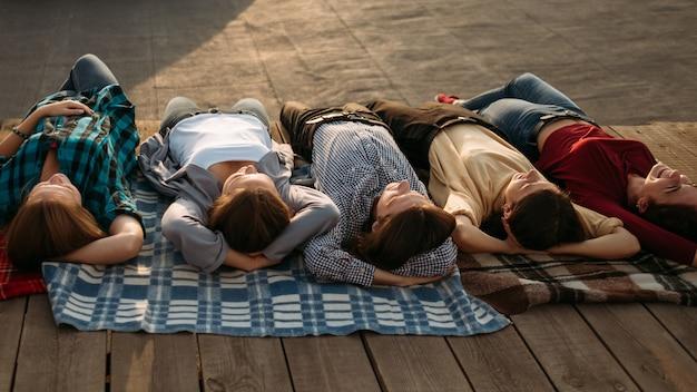 Medytacja relaksacyjna. nastolatki marzą o przyszłości. beztroska grupa młodych, różnorodnych ludzi marzących na jawie