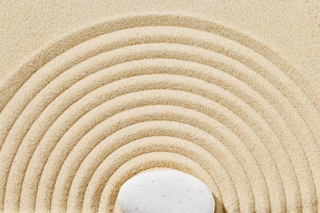 Medytacja w ogrodzie zen piaszczyste tło z kamiennym kopcem i okrągłymi liniami na piasku