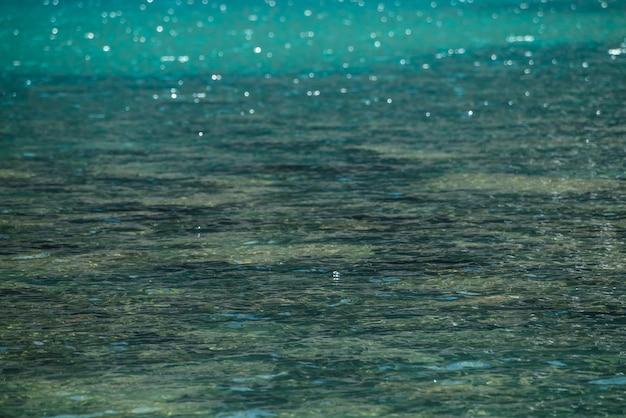 Medytacyjna fala i wiele odbitych świateł w zielonym górskim jeziorze.