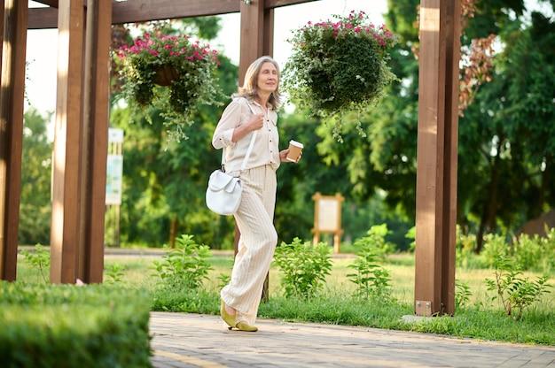 Medytacyjna kobieta z kawą spacerująca w parku