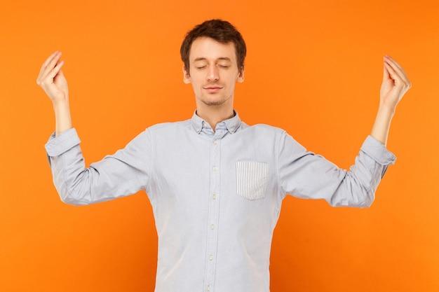 Medytacyjna praktyka umysłowa młody dorosły mężczyzna zamknął oczy i robi jogę