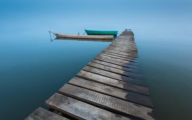 Medytacyjny krajobraz ze starym drewnianym molo i drewnianymi łodziami, długi czas ekspozycji, nieskończony horyzont