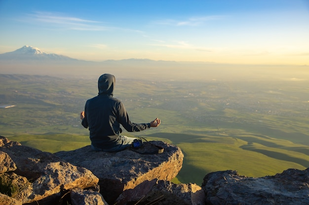 Medytując człowieka w górach o zachodzie słońca