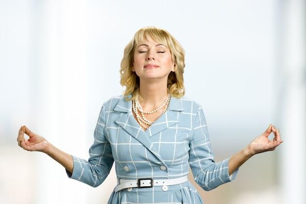 Medytująca dojrzała kobieta, tryb zen. pani w średnim wieku praktykuje jogę z zamkniętymi oczami.