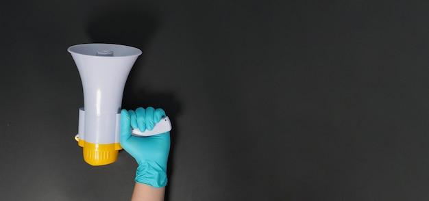 Megafon w ręku i na sobie niebieskie lateksowe rękawiczki na czarnym tle. strzelanie studyjne.