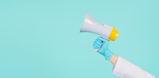 Megafon w ręku. mężczyzna nosić suknię lekarską i niebieskie rękawiczki medyczne na miętowym zielonym lub tiffany blue tle. strzelanie studyjne.