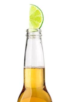 Meksykańska butelka piwa z plasterkiem limonki i mrozem na białym tle