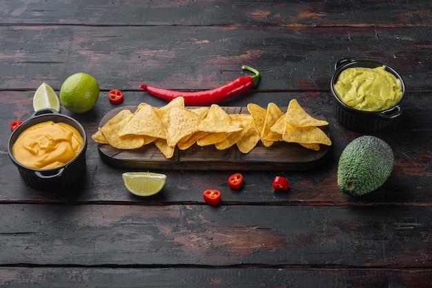 Meksykańska chrupiąca przekąska, chipsy nachos i serowe sosy z awokado guacamole, na starym drewnianym stole