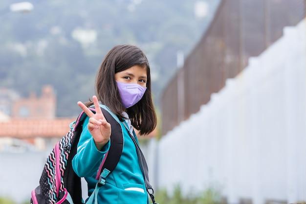 Meksykańska dziewczyna podekscytowana powrotem do szkoły nosząca maskę ochronną po zamknięciu koronawirusa