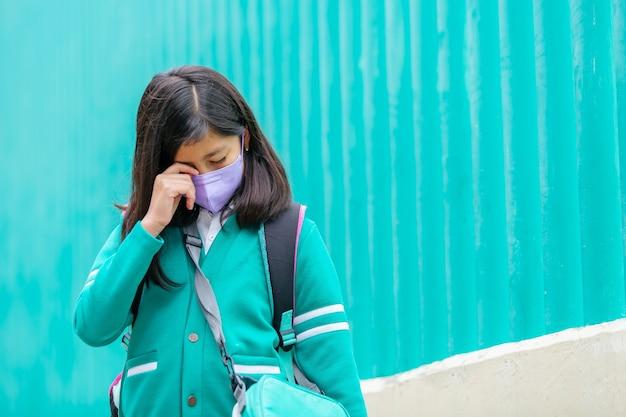 Meksykańska dziewczyna w mundurze i masce na twarzy płacze na plecach do szkoły, kopia przestrzeń