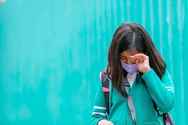 Meksykańska dziewczyna w mundurze i masce płacze na plecach do szkoły