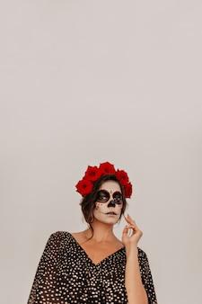 Meksykańska dziewczyna z różami w falowanych włosach tajemniczo w białym pokoju.
