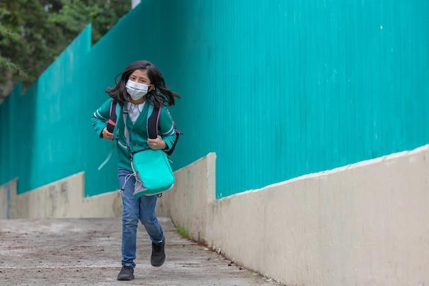 Meksykańska dziewczynka biegnąca z powrotem do szkoły w masce po pandemii koronawirusa