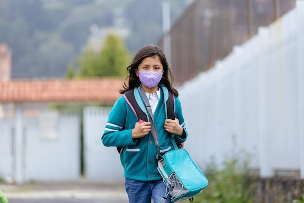 Meksykańska dziewczynka szczęśliwa wracająca do szkoły nosząca maskę na twarz