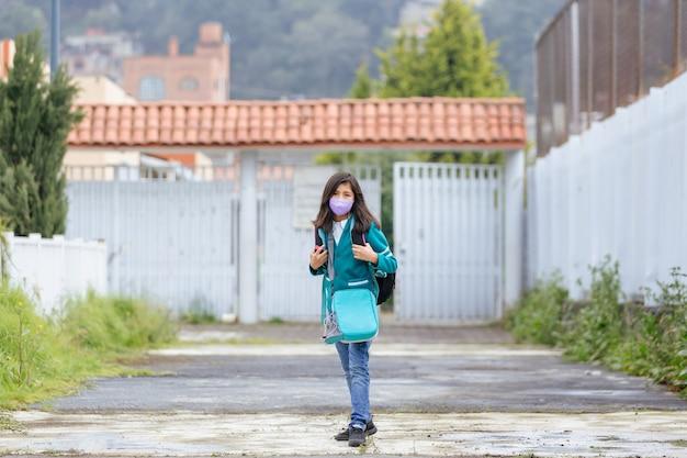 Meksykańska dziewczynka wraca do szkoły w masce po zablokowaniu pandemii koronawirusa