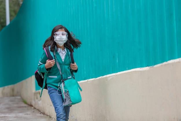 Meksykańska dziewczynka wraca do szkoły w plastikowej masce na twarz po pandemii koronawirusa