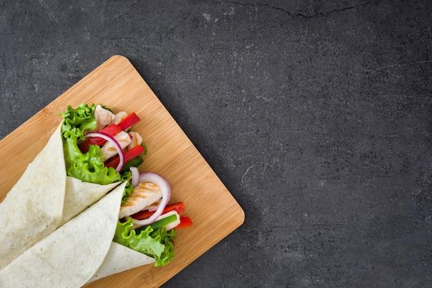 Meksykańska fajita z kurczakiem, papryką, cebulą i sałatą na łupkowym tle