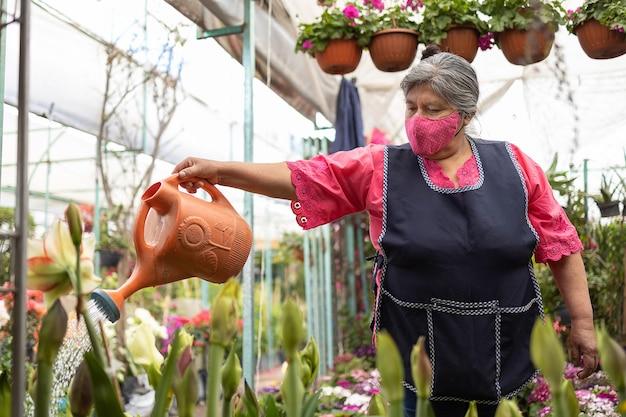 Meksykańska kobieta podlewa rośliny w szkółce xochimilco w meksyku, ma na sobie maskę, nowy normalny