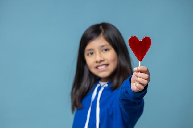 Meksykańska łacińska dziewczyna trzyma koncepcja miłości lizaka w kształcie serca