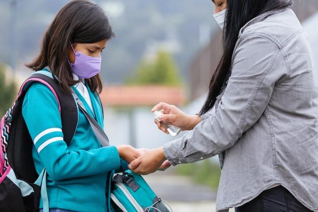 Meksykańska matka dezynfekuje córkę przed wejściem do szkoły