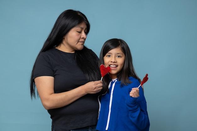 Meksykańska matka i córka dzielą się lizakiem w kształcie serca