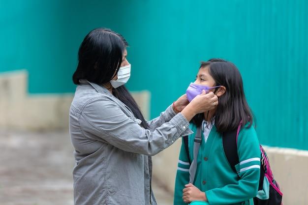 Meksykańska matka i córka noszą ochronną maskę na plecach do szkoły