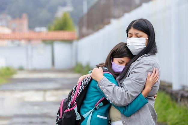 Meksykańska matka przytulająca córkę w drodze powrotnej do szkoły po zablokowaniu pandemii koronawirusa