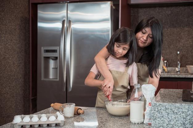 Meksykańska matka uczy swoją córkę gotowania w kuchni w dzień matki