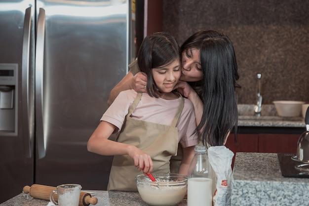Meksykańska matka uczy swoją córkę gotowania w kuchni