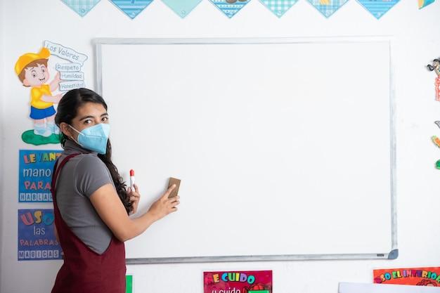 Meksykańska młoda nauczycielka nosząca maskę na plecach do szkoły po pandemii koronawirusa