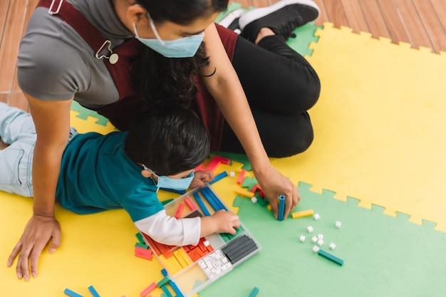 Meksykańska nauczycielka z maską na twarz opiekująca się dzieckiem i bawiąca się z maską w szkole