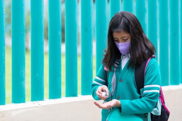 Meksykańska uczennica używa środka dezynfekującego przed powrotem do szkoły
