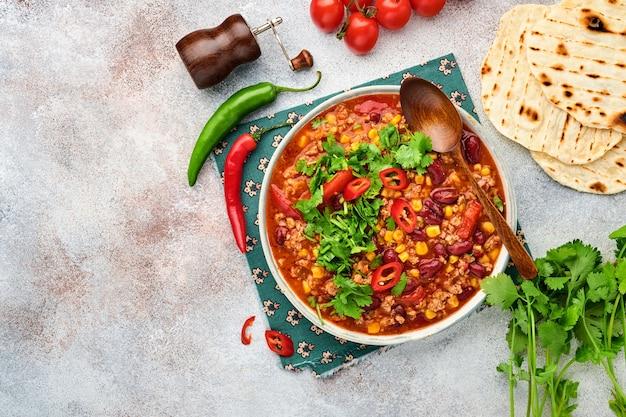 Meksykańska zupa z czarnej fasoli z mięsem mielonym, pomidorem, kolendrą, awokado i gulaszem warzywnym na jasnoszarym tle łupkowym, kamiennym lub betonowym. tradycyjne danie meksykańskie. widok z góry z miejsca na kopię.