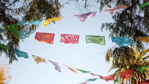 Meksykański baner papel picado, papierowa girlanda festiwalowa. wielobarwne flagi bibułkowe, ameryka łacińska.