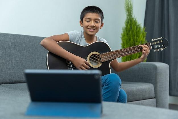Meksykański chłopak bierze lekcje gry na gitarze w domu z powodu blokady koronawirusa, nauki w domu