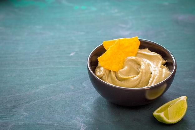 Meksykański dip guacamole w misce z chrupiącymi nachos na drewnianym tle. miejsce na tekst. tradycyjny sos z awokado.