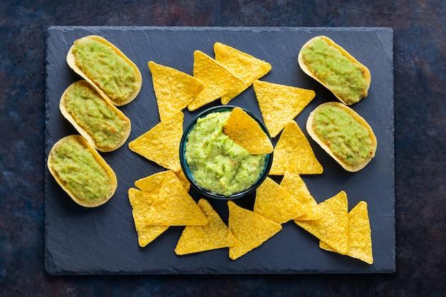 Meksykański sos guacamole z chipsami nachos na łupkowej desce. chipsy tortilla i guacamole na ciemnym tle. skopiuj miejsce. widok z góry