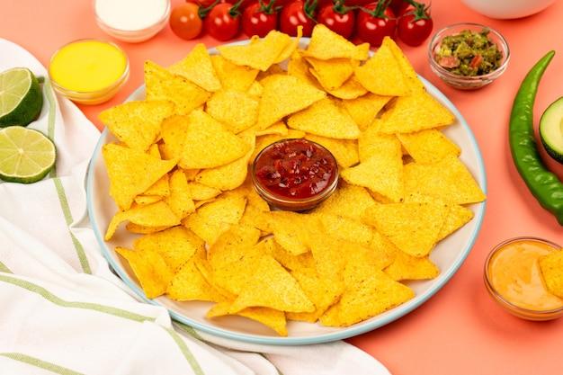 Meksykańskie chipsy kukurydziane nachos na talerzu z sosem i warzywami kuchnia meksykańska