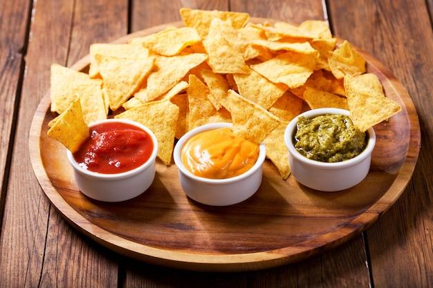 Meksykańskie chipsy kukurydziane nachos z guacamole, salsą i dipem serowym na drewnianym stole